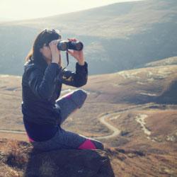 Mujer mirando por unos prismáticos